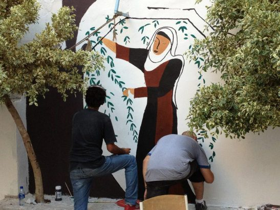 This mural at the UNRWA Ras Al Ain school in Sabra, Beirut, depicts a Palestinian woman in traditional dress picking olives. UNRWA schools stopped teaching Palestinian history after the Lebanese government prevented such classes. The Ma'an Youth Group created the mural as a way of representing Palestinian history on the walls of their camp and school.