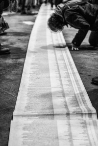 A list of over 20,000 migrants who lost their lives at Europe's borders, rolled out at the Berlin Hauptbahnhof. Photograph by Andrea Linss.