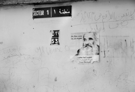 Secteur 1, Dbayeh refugee camp, Lebanon. A poster of the Saint Abouna Jacoub, on a wall with graffitti at the camp. Dbayeh differs from other refugee camps due to the fact that it is a permanent arrangement. The residents remain stateless under Lebanese law, and no sign of a change appears to be on the horizon.