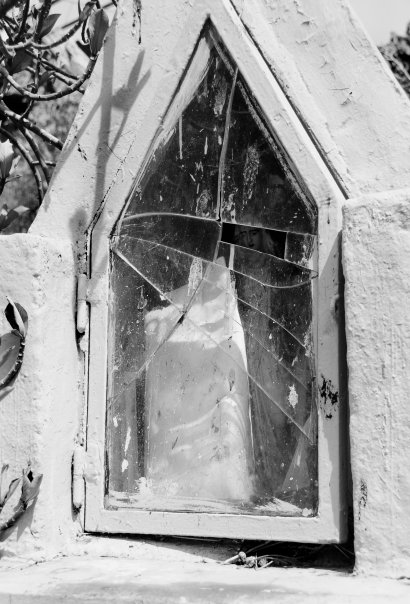 The face of Our Lady visible through the broken glass on this niche.